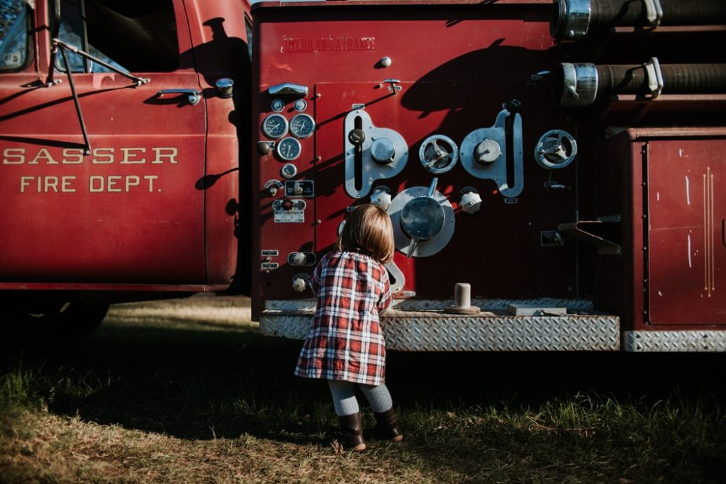 A child standing in front of a fire truck.