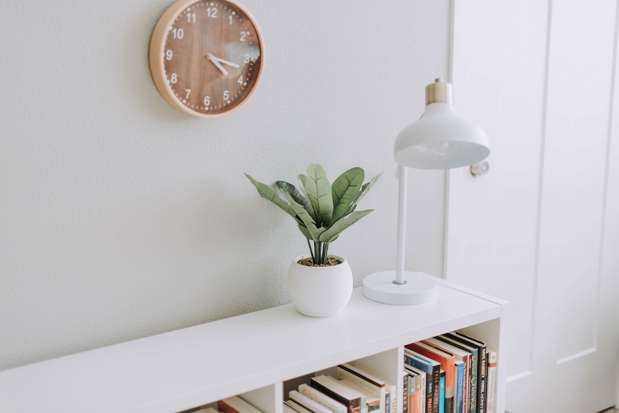 Book shelf with plant, lamp, and clock