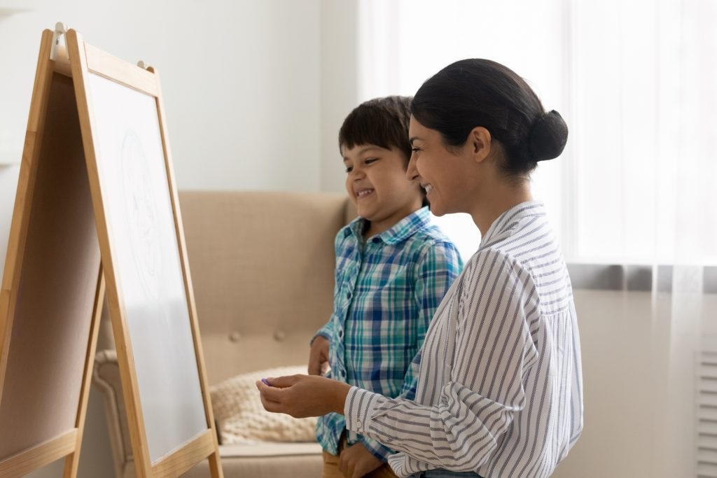 Mother and son painting on an easel for Mother's Day