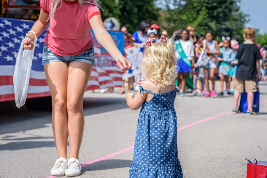 Woman handing a little girl candy in 4th of July parade