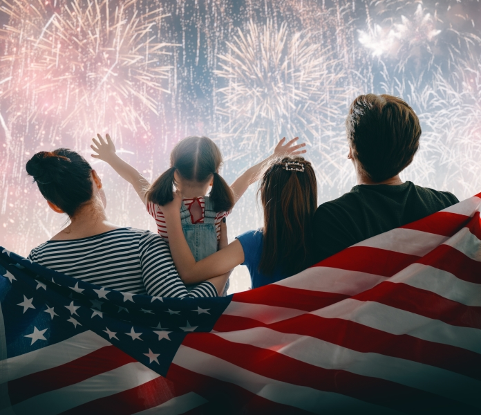Family of 4 watching fireworks while in front of American Flag