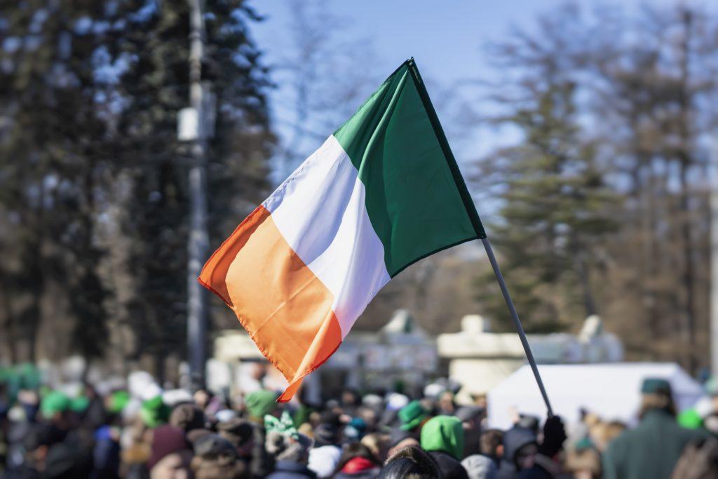 Irish flag waving above celebrating crowd.