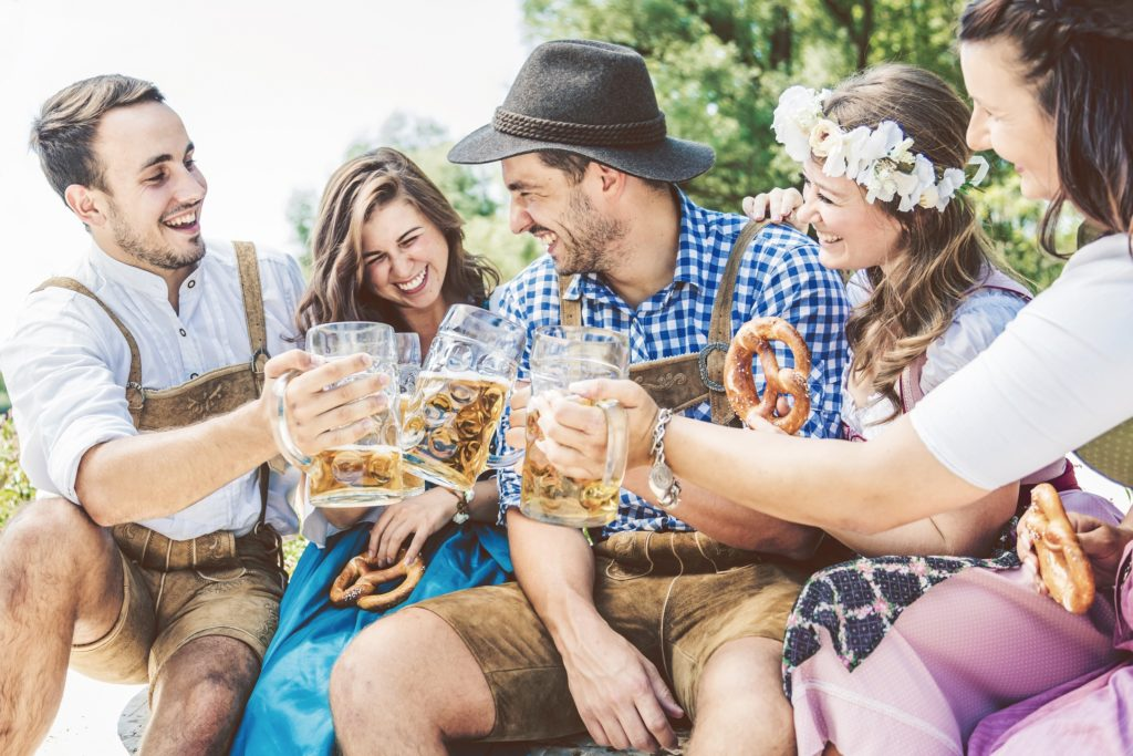 Five friends eating pretzels and drinking beer, dressed up for Oktoberfest