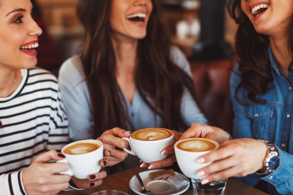 Three women chatting and drinking coffee