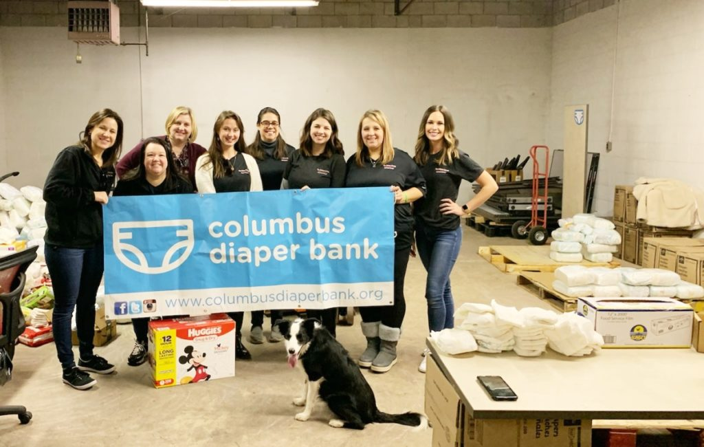 Volunteers in sorting diapers and a dog.