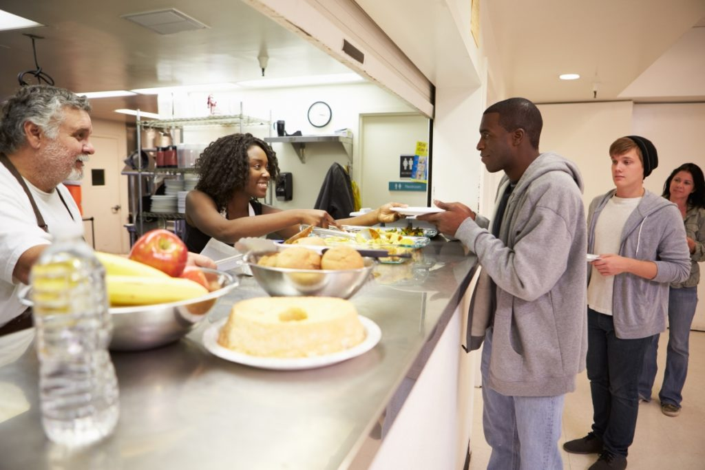 Young adults receiving food at a shelter.